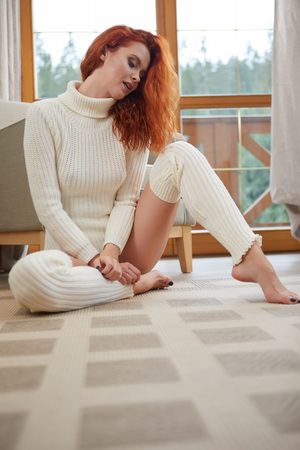 Beautiful autumn red hair model with waving glow hair.Sun light on sunset. Portrait of romantic female in sweater. Stock Photo
