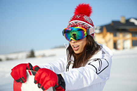 Sporty female holds snowboard in mountains 版權商用圖片