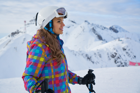 adult woman skier close up portrait wearing white helmet with mask in snow winter mountain Banque d'images