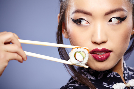 Sushi woman holding sushi with chopsticks looking at the camera smiling.