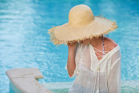 Fashion beautiful woman on summer vacation relaxing at luxury resort spa poolside. Young fashionable lady wearing sun hat