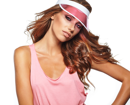 studio shoot of a summer woman wearing pink plastic visor cap