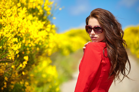 Beautiful woman in red dress on yellow flowers background Banque d'images