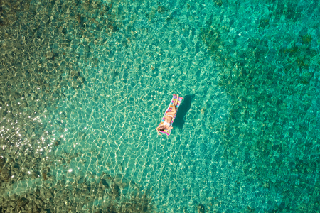 Top down view of a beautiful woman in a white bikini who is floating on a air mattress
