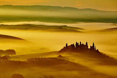 Scenic Tuscany landscape with rolling hills and valleys in golden morning light Imagens