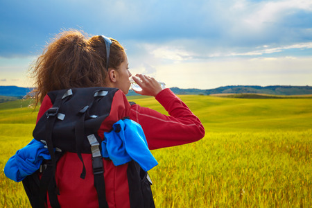 Tourist girl enjoying view of beautiful dry green wheat hills, traveling along Europe in summer season, active lifestyle concept