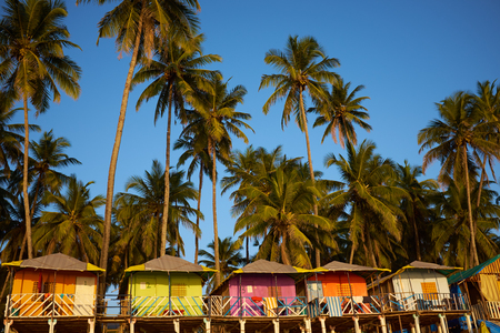 Colorful huts on the sandy beach with palm trees  in Goa, India 免版税图像