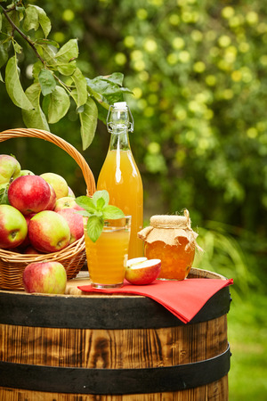 apples on background orchard standing on a barrel. Apple juice and apple preserves. 스톡 콘�츠