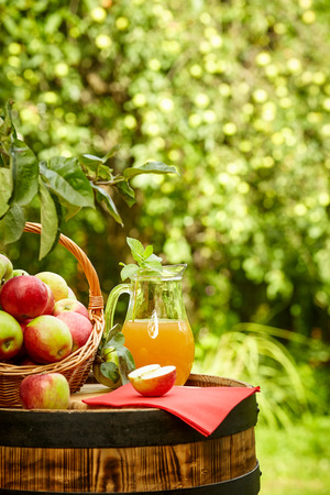 apples on background orchard standing on a barrel. Apple juice and apple preserves. Foto de archivo