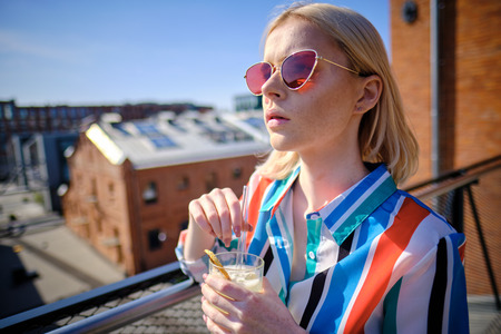 the girl is drinking a cocktail at the rooftop bar