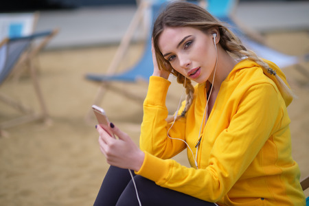 Young woman in sports outfit resting and listening music on smartphone after running in the city.