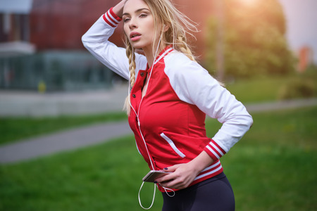 Sport  pretty woman listens to music in headphones