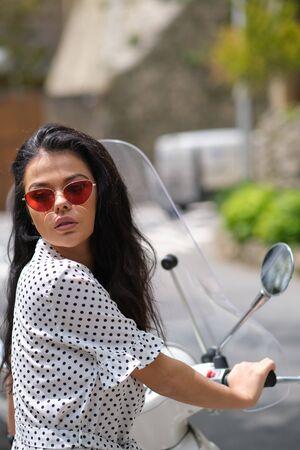 beautiful italian woman sitting on a italian scooter in Italy town