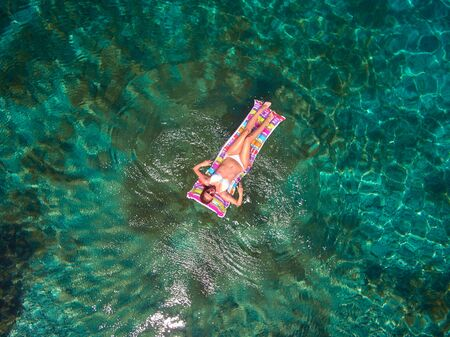 aerial view of a beautiful young woman in bikini on a matress in the sea Stockfoto