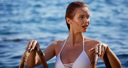 redhair woman in bikini relaxed on quiet sea with warm sunset colors. Reklamní fotografie
