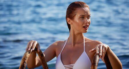 Rothaarige Frau im Bikini entspannt auf ruhigem Meer mit warmen Sonnenuntergangsfarben. Standard-Bild