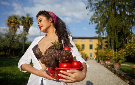 La Dolce Vita-Lebensstil. Eine Italienerin trägt einen Korb mit Gemüse. Haus und Garten im Hintergrund Standard-Bild