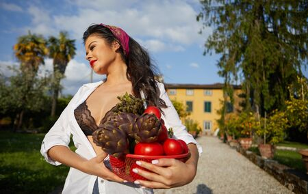 La dolce vita lifestyle. An Italian woman is carrying a basket with vegetables. House and garden in the background