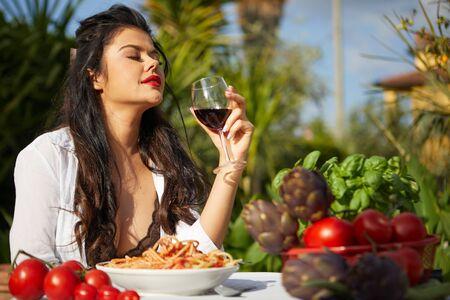 Sexy Italian eats spagetti on the garden terrace