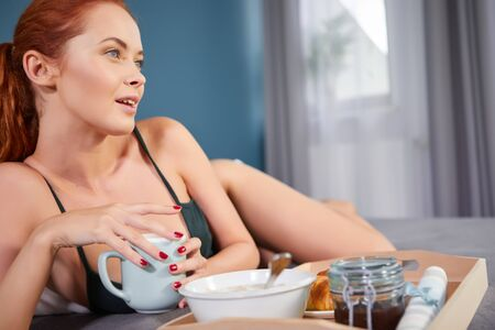 Beautiful happy redhead woman having breakfast in bed Stockfoto