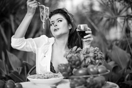 bw vintage portrait of a italian lifestyle  woman eating italian pasta with tomato sauce and parmesan, served with glass of wine Banco de Imagens