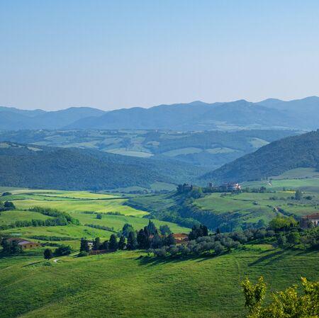 Tipico paesaggio toscano con colline, alberi verdi e case, Italia. Archivio Fotografico