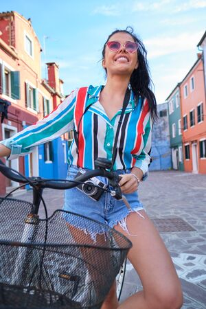 Woman with vintage camera riding retro bicycle on a colorful italian city street