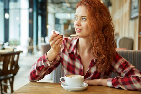 Happy young woman drinking coffee / tea  in a coffee shop 写真素材