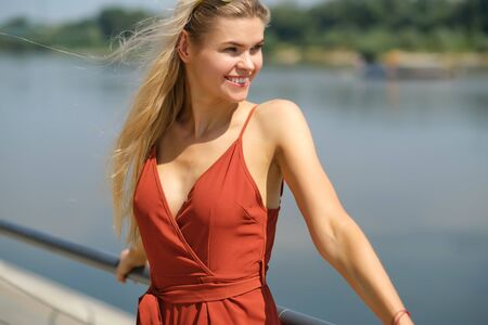 Beautiful woman in red dress. City river background. Imagens