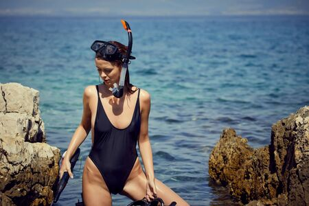 sexy woman with fins and crossbow is preparing to hunt for fish
