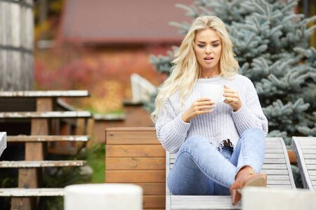 Blonde young girl  looking side, sitting on home terrace, holding cup tea