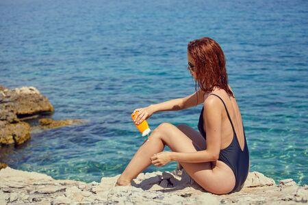 sexy young woman on the beach applying sun cream Фото со стока
