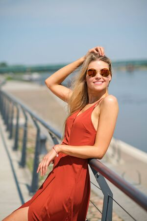gorgeous beautiful woman in long red  dress and  hat walking.  Portrait of happy girl in the morning outdoors