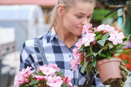 Young woman gardening in greenhouse.She smelling flowers. Фото со стока