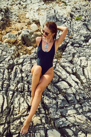 Girl in a swimsuit on the beach, the Adriatic coast, the mountains of Croatia