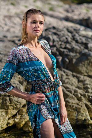 Fashionable woman posing on a beach with rocks in a long dress Standard-Bild