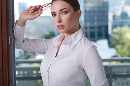 Jonge zakenvrouw (makelaar in onroerend goed) die vrijstaand modern kantoor presenteert