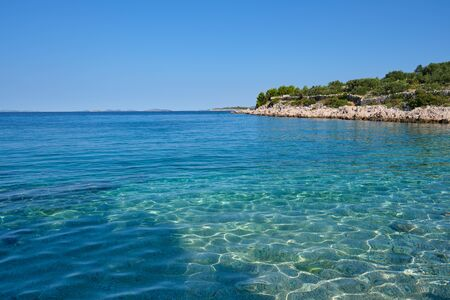 Crystal clear blue green Adriatic sea and a rocky beach on the island Krk, Croatia,