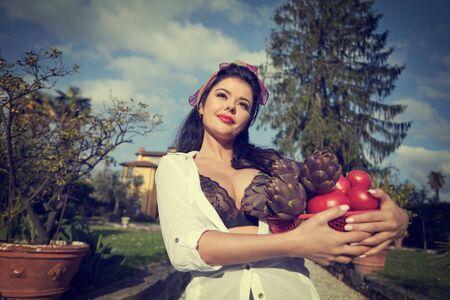 La Dolce Vita-Lebensstil. Eine Italienerin trägt einen Korb mit Gemüse. Haus und Garten im Hintergrund