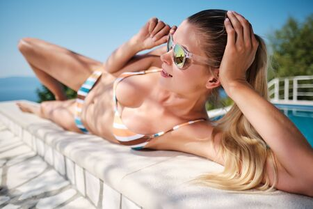 portrait of sensual glamour model getting sunbathe near private pool, mirrored sunglasses, tanned skin, bright make up. Luxury vacation concept. Фото со стока