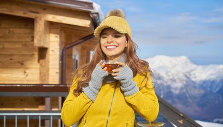 Woman drinking warm tea in the rustic wooden terrace on mountain, winter alpine view, snow on peak