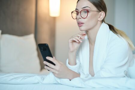 Beautiful young woman in bathrobe having rest on comfortable bed room after spa procedures. She is typing message on smartphone and smiling. Lady lies on comfortable bed and uses smartphone.