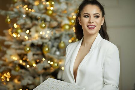 Smiling young woman with christmas present box near christmas tree Stock fotó