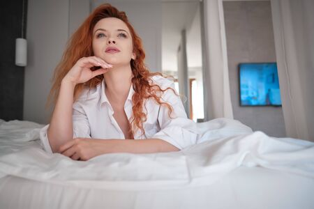 Smiling and looking forward. Hot redhead girl sits on the white bed Stock fotó