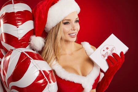 Christmas party.Happy excited young woman in santa claus hat with balloons over red background