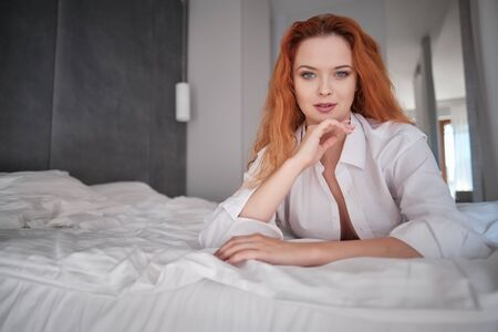 very sensual woman in sexy pose on bed with long natural redhair, open shirt and white panties Stock fotó