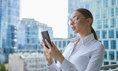 Beautiful business woman with smartphone on the background of the modern office