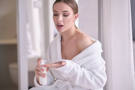 Beautiful young woman after bath applying body cream onto skin at home Archivio Fotografico - 135269428
