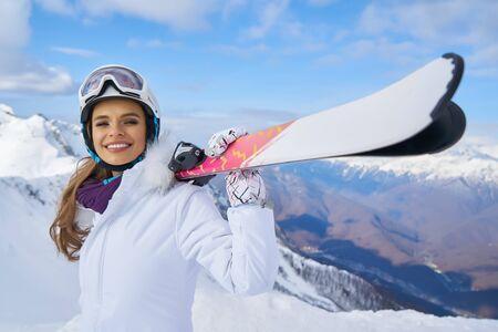 Nahaufnahmeporträt des schönen Skifahrermädchens, das Maske trägt und Ski hält und Winterferien genießt