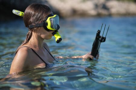 Aqua woman diver spearfishing gun.